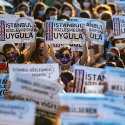 Los manifestantes con máscaras protectoras sostienen pancartas durante una manifestación para una mejor implementación de la Convención de Estambul y la Ley turca 6284 para la protección de la familia y la prevención de la violencia contra las mujeres, en Estambul, Turquía.   Foto:Yasin Akgul / AFP
