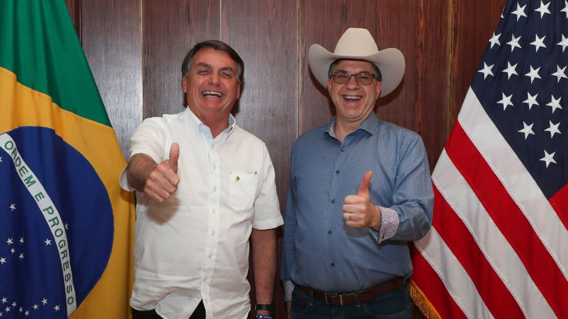 In this photo distributed by Brazil's presidential press office, Brazilian President Jair Bolsonaro, left, and US Ambassador Todd Chapman pose for a photo during an event to mark US Independence Day at the ambassador's residence in Brasilia, Brazil, Saturday, July 4, 2020.