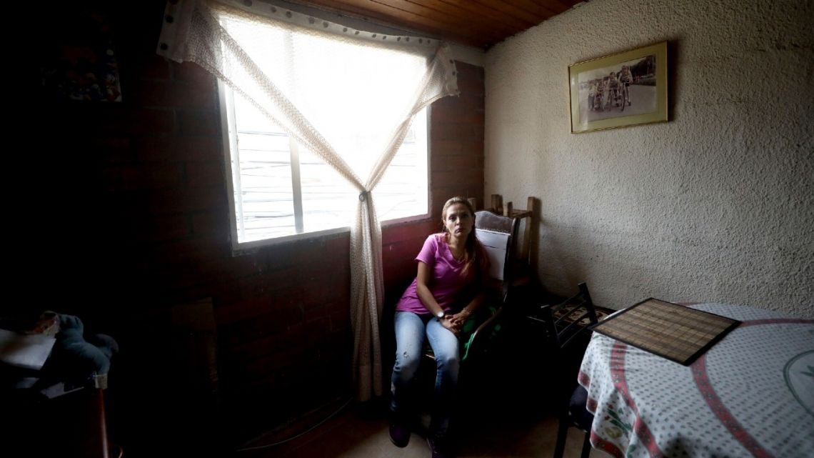 Myriam Roncancio, 35, who is living with her parents after breaking up with her husband of 10 years, sits in a chair during an interview in the Soacha borough of Bogotá, Colombia, Tuesday, July 28, 2020. After she lost her job as a restaurant administrator at the start of the new coronavirus outbreak and her husband lost his as a baggage handler at Bogotá's airport, they were unable to pay their rent and their quarrelling became more frequent. That's when he left, she says.