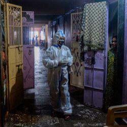 Un trabajador de la salud que usa un traje de Equipo de Protección Personal (EPP) interactúa con un residente durante un examen de coronavirus COVID-19 puerta a puerta en el área de los barrios marginales de Dharavi en Mumbai. | Foto:INDRANIL MUKHERJEE / AFP