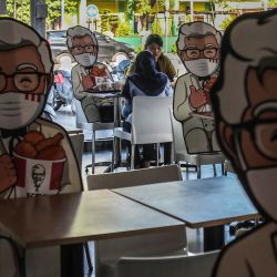 Los visitantes de un restaurante de comida rápida comparten un asiento con el recorte del coronel Sanders como un esfuerzo para forzar un distanciamiento físico como medida para prevenir la propagación del coronavirus COVID-19 en Medan, Sumatra del Norte. | Foto:IVAN DAMANIK / AFP