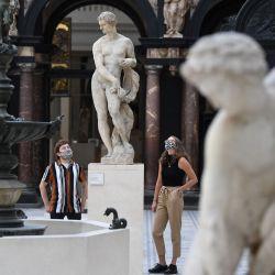 Empleados del museo que llevan una máscara facial o se cubren debido a la pandemia de COVID-19, posan frente a una estatua titulada 'Zephyr' 1576, del artista Pietro Francavilla, durante un photocall en el museo Victoria and Albert (V&A) de Londres. | Foto:DANIEL LEAL-OLIVAS / AFP