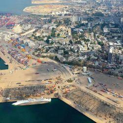 Una vista aérea muestra un barco tendido de costado en el puerto de Beirut, tres días después de una colosal explosión de una enorme pila de nitrato de amonio que había languidecido durante años en un almacén del puerto y dejó decenas de personas muertas o heridas. y causó devastación en la capital libanesa. | Foto:AFP