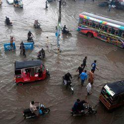 Los viajeros se abren paso a lo largo de una calle inundada después de las fuertes lluvias monzónicas en la ciudad portuaria de Karachi en Pakistán. | Foto:Asif Hassan / AFP