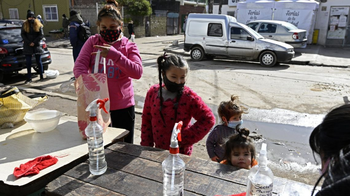 "A family collects free meals at the Caacupe Virgin parish church, led by Argentine priest Lorenzo De Vedia, aka ""Padre Toto"", at the Villa 21 shantytown in Buenos Aires, on July 24, 2020, amid the lockdown measures against the spread of the Covid-19 coronavirus."