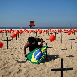 Un manifestante con una bandera brasileña es visto junto a cruces durante un homenaje a las víctimas del COVID-19 organizado por la ONG Río de Paz en la playa de Copacabana en Río de Janeiro, Brasil. | Foto:MAURO PIMENTEL / AFP