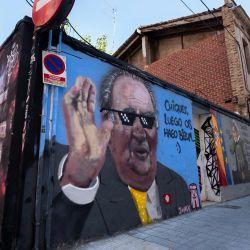 Una pareja pasa junto a un graffiti del artista valenciano J.Warx que representa al ex rey español Juan Carlos diciendo  | Foto:JOSE JORDAN / AFP