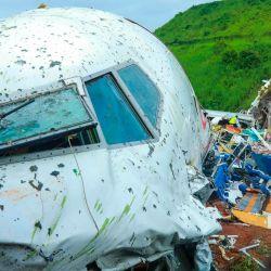 Las autoridades inspeccionan los restos de un avión de Air India Express en el Aeropuerto Internacional de Calicut en Karipur, Kerala. - Fuertes lluvias y vientos azotaron un avión que transportaba a 190 personas antes de que se estrellara y se partiera en dos en un aeropuerto en el sur India, matando al menos a 18 personas e hiriendo a decenas más, dijeron las autoridades. | Foto:Arunchandra Bose/ AFP