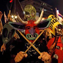 Un manifestante con una máscara de papel maché de demonio con cuernos sostiene baquetas cruzadas mientras está flanqueado por otro manifestante que lleva una máscara en forma de calavera y carteles que muestran cabezas de extraterrestres levantadas detrás, durante una manifestación contra el gobierno israelí cerca de la residencia del primer ministro. en Jerusalén. | Foto:Ahmad GHARABLI / AFP