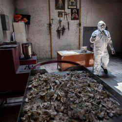 Un empleado usa equipo de protección mientras trabaja en el crematorio de Azcapotzalco en la Ciudad de México, en medio de la pandemia del coronavirus COVID-19. | Foto:PEDRO PARDO / AFP