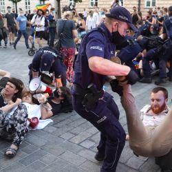 Los agentes de policía impiden que los activistas LGBT bloqueen la carretera a un vehículo policial que transportaba al activista de los derechos de los homosexuales Margo en Varsovia, Polonia. | Foto:JANEK SKARZYNSKI / AFP