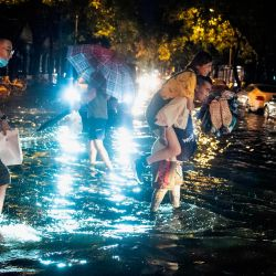 Un hombre lleva a cuestas a una mujer para cruzar una calle inundada después de una lluvia repentina en Beijing. | Foto:NOEL CELIS / AFP