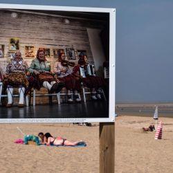 La gente disfruta de la playa con una fotografía de la serie fotográfica  | Foto:JOEL SAGET / AFP