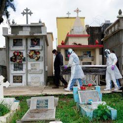Sepultureros vestidos con trajes de bioseguridad y familiares trasladan un ataúd con los restos de una víctima del COVID-19 en el cementerio municipal de Mixco, en Mixco, a 20 km al oeste de la ciudad de Guatemala. | Foto:Johan Ordonez / AFP