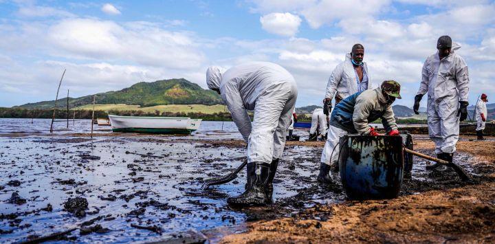 Personas extraen aceite derramado del buque MV Wakashio, perteneciente a una empresa japonesa pero con bandera panameña, que encalló y provocó una fuga de petróleo cerca del Blue Bay Marine Park en el sureste de Mauricio.