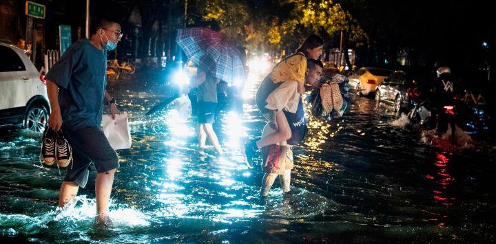 Un hombre lleva a cuestas a una mujer para cruzar una calle inundada después de una lluvia repentina en Beijing.