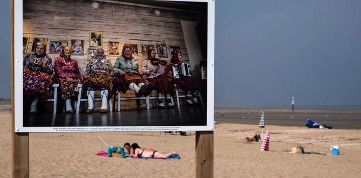 La gente disfruta de la playa con una fotografía de la serie fotográfica