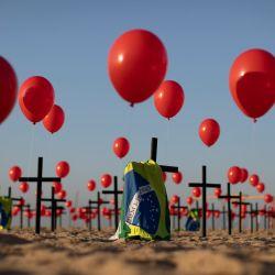 Brasil, Río de Janeiro: banderas brasileñas y globos rojos unidos a 100 cruces, por la ONG Río de Paz, en la playa de Copacabana, en memoria de las víctimas que murieron por coronavirus. | Foto:Fernando Souza / DPA