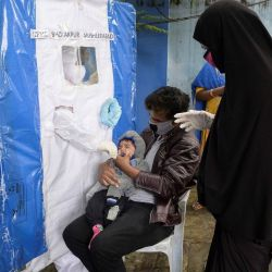 Un trabajador de la salud toma una muestra de hisopo de un niño en una caseta de prueba de coronavirus COVID-19 improvisada y gratuita en Hyderabad. | Foto:Noah Seelam / AFP
