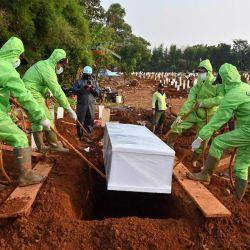 Los sepultureros bajan un ataúd durante un funeral por las víctimas del coronavirus COVID-19 en el cementerio Pondok Ranggon en Yakarta. | Foto:ADEK BERRY / AFP