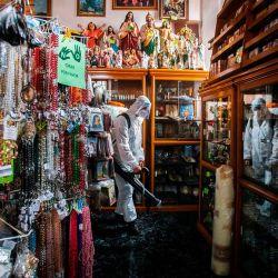 Un trabajador de limpieza que usa equipo de protección personal desinfecta en la tienda de la catedral de Morelia, en el estado de Michoacán, en medio de la pandemia del nuevo coronavirus. | Foto:ENRIQUE CASTRO / AFP