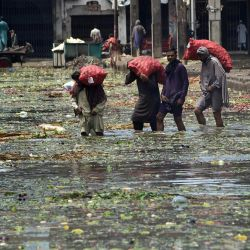 Los trabajadores atraviesan un mercado de frutas y verduras inundado después de las fuertes lluvias monzónicas en Lahore. | Foto:Arif Ali / AFP