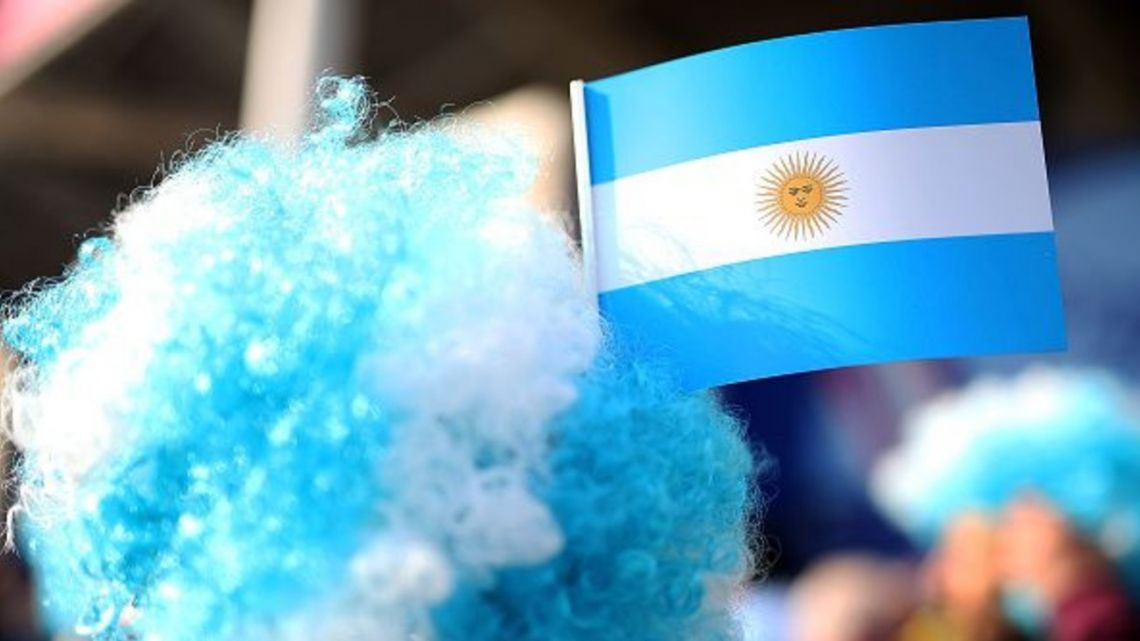 A man wears a wig with an Argentine flag.