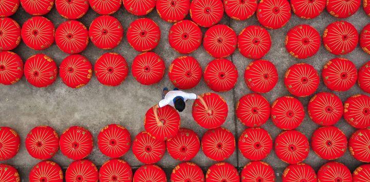 China, Taizhou: un trabajador coloca linternas rojas chinas tradicionales terminadas en un taller.