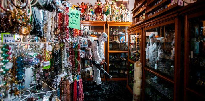 Un trabajador de limpieza que usa equipo de protección personal desinfecta en la tienda de la catedral de Morelia, en el estado de Michoacán, en medio de la pandemia del nuevo coronavirus.