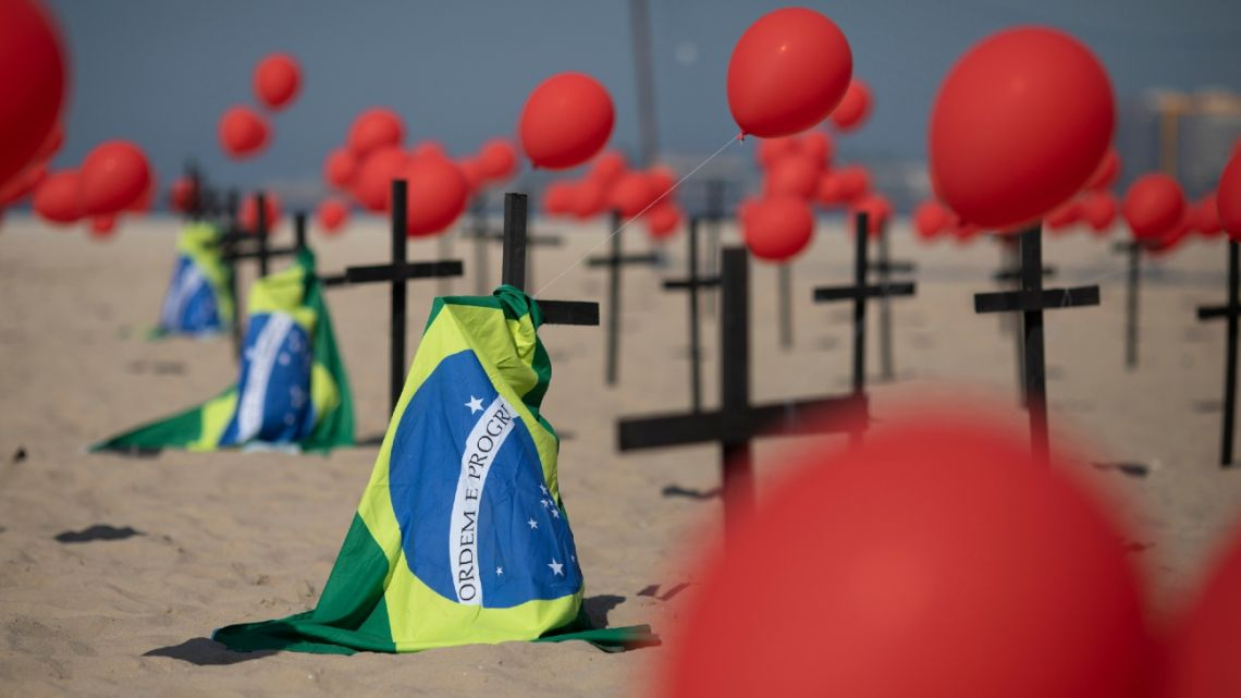 Crosses, red balloons and Brazilian nation flags are placed in the sand on Copacabana beach in a demonstration organised by Rio de Paz to honour the victims of Covid-19, as the country heads to a milestone of 100,000 new coronavirus related deaths, in Rio de Janeiro, Brazil, Saturday, Aug. 8, 2020.