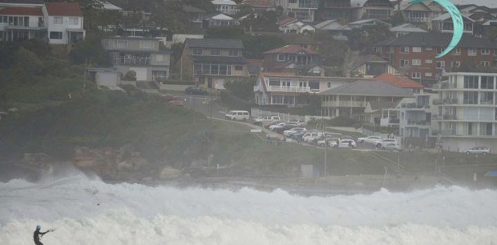 La gente practica kitesurf en mares agitados frente a las playas del norte de Sydney.