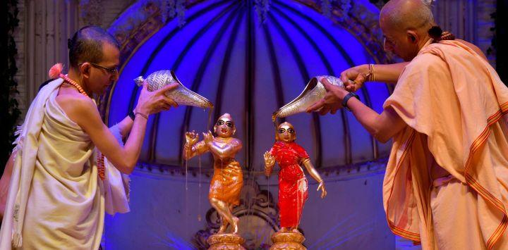 Sacerdotes hindúes bañan a los ídolos de los dioses hindúes Krishna (izquierda) y su consorte Radha en miel durante el 'Abhisheka', ritual de unción sagrada, que se lleva a cabo como parte de las celebraciones de Krishna Janmashtami en el templo de la Sociedad Internacional de Conciencia de Krishna en Bangalore.