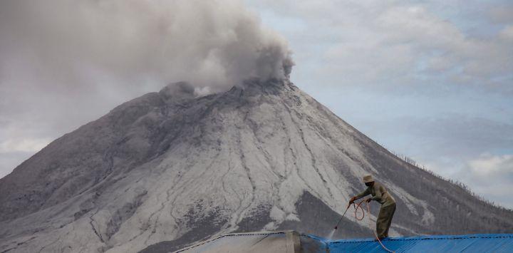 Un aldeano limpia la ceniza volcánica de su techo en la aldea de Naman Teran en Karo, en el norte de Sumatra, un día después de la erupción del monte Sinabung (al fondo).