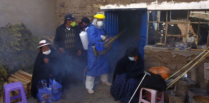 Un empleado funerario con equipo de protección desinfecta la casa de una víctima de COVID-19 mientras los familiares lloran afuera, antes de llevar el ataúd al cementerio local para su entierro en el remoto pueblo aymara de Acora, en las tierras altas, a una hora de la ciudad de Puno, cerca de la frontera con Bolivia.