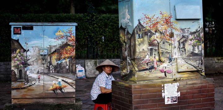 Un vendedor espera a los clientes sentado detrás de los gabinetes de electricidad decorados con pinturas a lo largo de una calle en Hanoi.