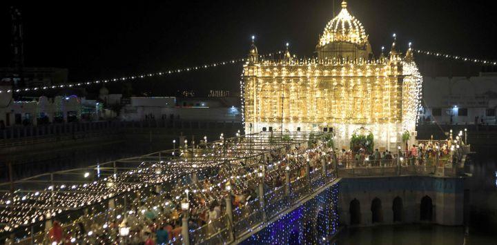Los devotos hindúes llegan para presentar sus respetos con motivo del festival 'Janmashtami' que marca el nacimiento del dios hindú Krishna, en el iluminado Templo Durgiana en Amritsar.