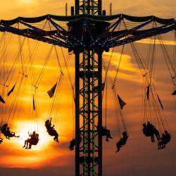 Baviera, Múnich: la gente monta un carrusel de cadenas en el Parque Olímpico durante la puesta de sol. | Foto:Sven Hoppe / DPA