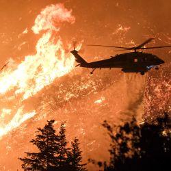 EE. UU., Lago Hughes: un helicóptero de extinción de incendios arroja agua sobre las llamas que arden a través del bosque en medio de incendios forestales que han quemado más de 10,000 acres. | Foto:DPA