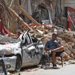 Un libanés habla por teléfono mientras está sentado junto a los escombros de un edificio tradicional destruido en el barrio de Gemmayzeh, tras la catastrófica explosión del puerto la semana pasada que devastó la capital Beirut. | Foto:AFP