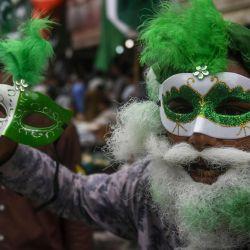 Un vendedor con una máscara con los colores de la bandera nacional de Pakistán sostiene otra máscara mientras espera a los clientes en un mercado en Karachi, antes del 74o Día de la Independencia del país, que marca el fin del dominio colonial británico. | Foto:Asif Hassan / AFP