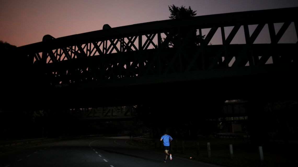 In this July 20, 2020 file photo, a man jogs during a government-ordered lockdown to curb the spread of the new coronavirus the first night after the city authorised outdoor exercise as part of rolling back restrictions in Buenos Aires