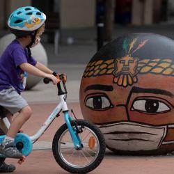 Un niño pasa en bicicleta junto a una obra del artista iraní Behzad Shafagh en las calles de Barcelona. | Foto:Josep Lago / AFP