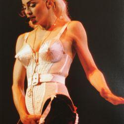 Con el icónico vestuario diseñado por Jean Paul Gaultier en 1990.