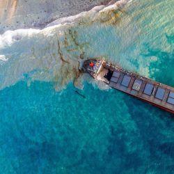Una vista aérea tomada muestra el buque MV Wakashio, perteneciente a una empresa japonesa pero con bandera panameña que encalló cerca del Blue Bay Marine Park, Mauricio hace tres semanas. | Foto:STRINGER / L'Express Maurice / AFP