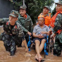Esta foto muestra a oficiales de policía paramilitares de China evacuando a un residente en una calle inundada luego de fuertes lluvias en Meishan en la provincia de Sichuan, suroeste de China. | Foto:STR / AFP