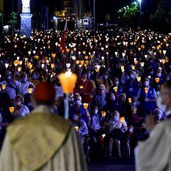 Los fieles que llevan mascarillas sostienen velas mientras asisten a la misa de peregrinación de la 147a Asunción en Lourdes. | Foto:GEORGES GOBET / AFP