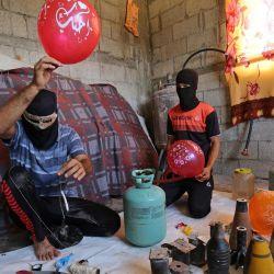 Palestinos enmascarados preparan objetos inflamables antes de sujetarlos a globos para volar hacia Israel, en Rafah, en el sur de la Franja de Gaza. | Foto:SAID KHATIB / AFP