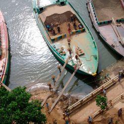 Una foto aérea muestra a los trabajadores descargando arena de un carguero del río Buriganga en Dhaka. | Foto:Munir Uz zaman / AFP