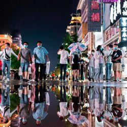 Las personas se reflejan en un charco después de una lluvia mientras caminan por un distrito comercial en Beijing. | Foto:NOEL CELIS / AFP