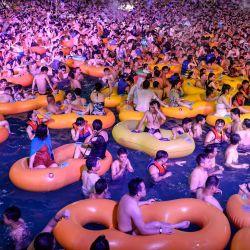 Esta foto tomada muestra a personas que ven una actuación mientras se refrescan en una piscina en Wuhan, en la provincia central china de Hubei. | Foto:STR / AFP